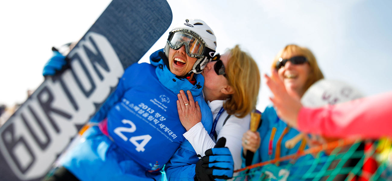 a woman kissing a snowboarder as others look on