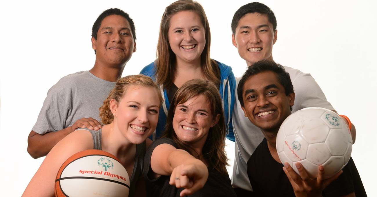 Six young people in sports gear and with sport balls smile