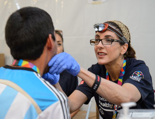 A woman with blue gloves and headlamp looks in an athlete's mouth