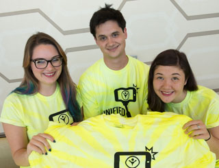Youth volunteers pose with brightly colored T-shirts