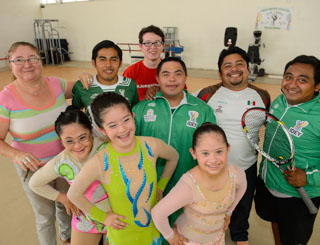 A group of athletes and volunteers in sports gear pose