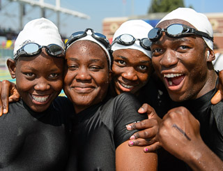 Four swimmers with joyous smiles pose