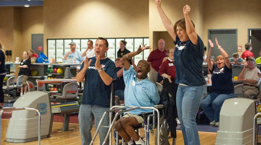 an Athlete in a wheelchair with  two volunteers cheering the athlete on in the bowling ally