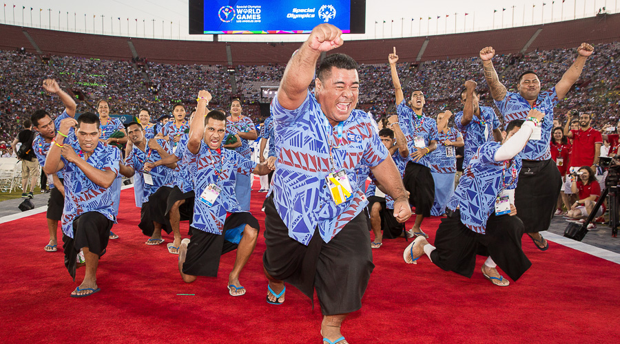 A team of athletes in tropical shirts cheer in unison
