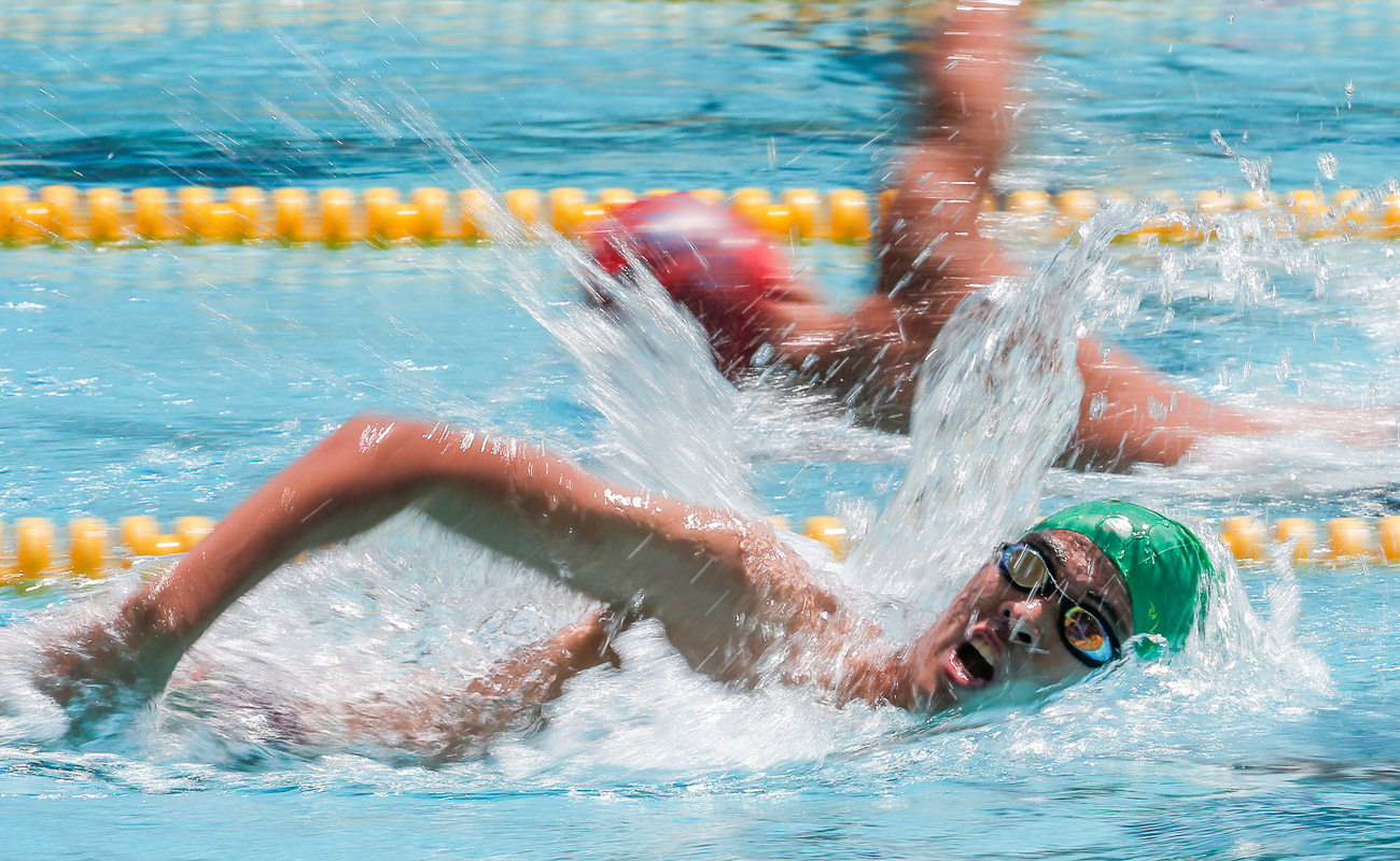 two men swimming in the pool in a race