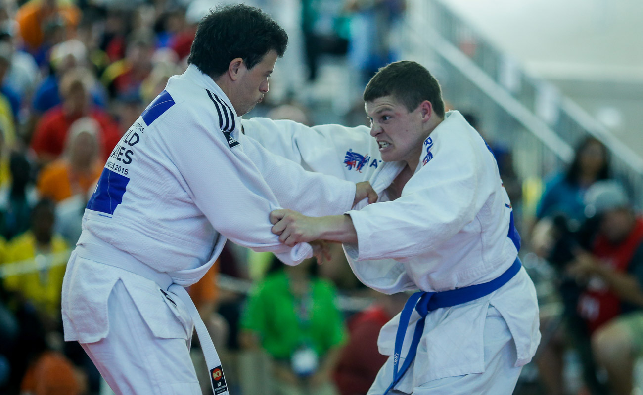 two men in blue and white doing judo move
