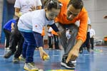 a man shows a young girl where to put a ball