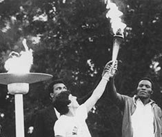 Black and white photo of men holding a flaming torch high above their heads