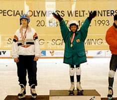 Athletes on a medal stand in winter coats. The year 1993 is visible on a banner