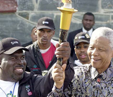 Two men, one of them Nelson Mandela, the other a Special Olympics athlete named Ricardo Thornton, hold a flaming torch.