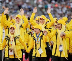 A group of athletes in bright yellow jerseys cheer