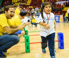 A volunteer cheers for a very young girl going through an obstacle course.