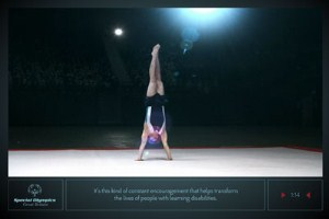 Special Olympics Athlete Omar does a handstand on a stage