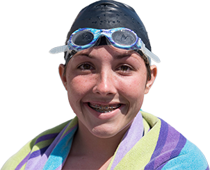 A young woman in a swim cap and with a towel over her shoulders smiles