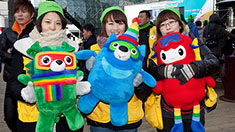 Three people hold colorful stuffed mascot dolls