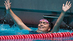A swimmer with her hands in the air after finishing