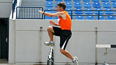 A man in orange jumping over a hurdle in a stadium