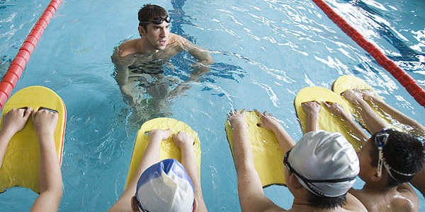 Swimmer Michael Phelps instructs swimmers in a pool
