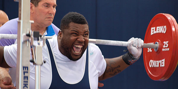 Powerlifter hoists a big weight with a grimace