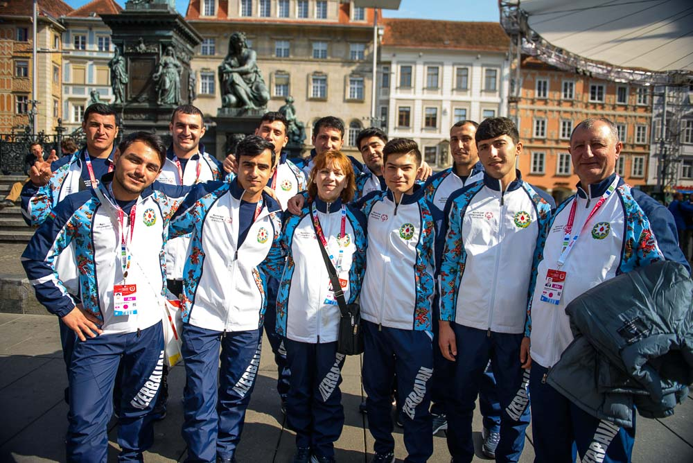 Host Town in Graz A team dressed in white pose with statues and buildings in the background.
