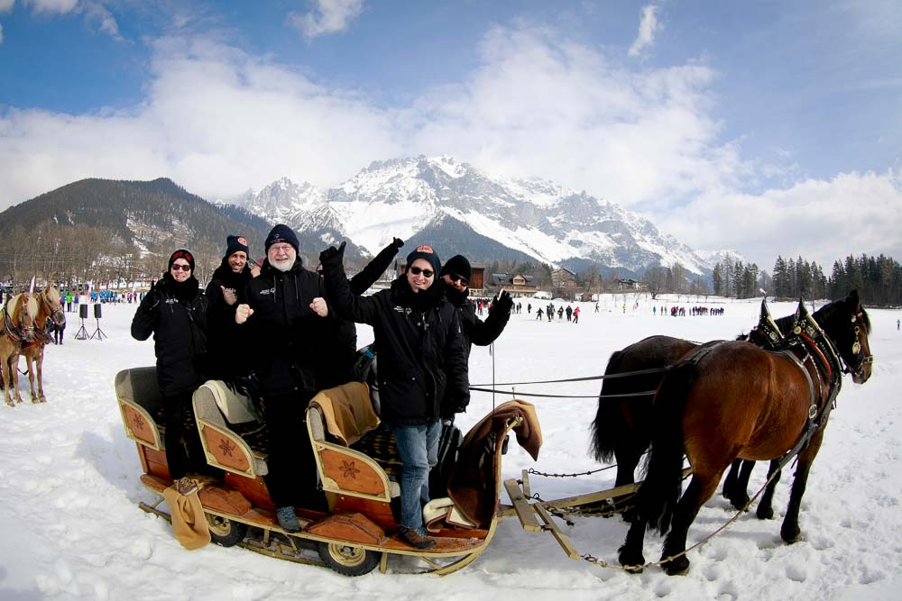 Four people in heavy black coats stand and pose in a horse-drawn sled.