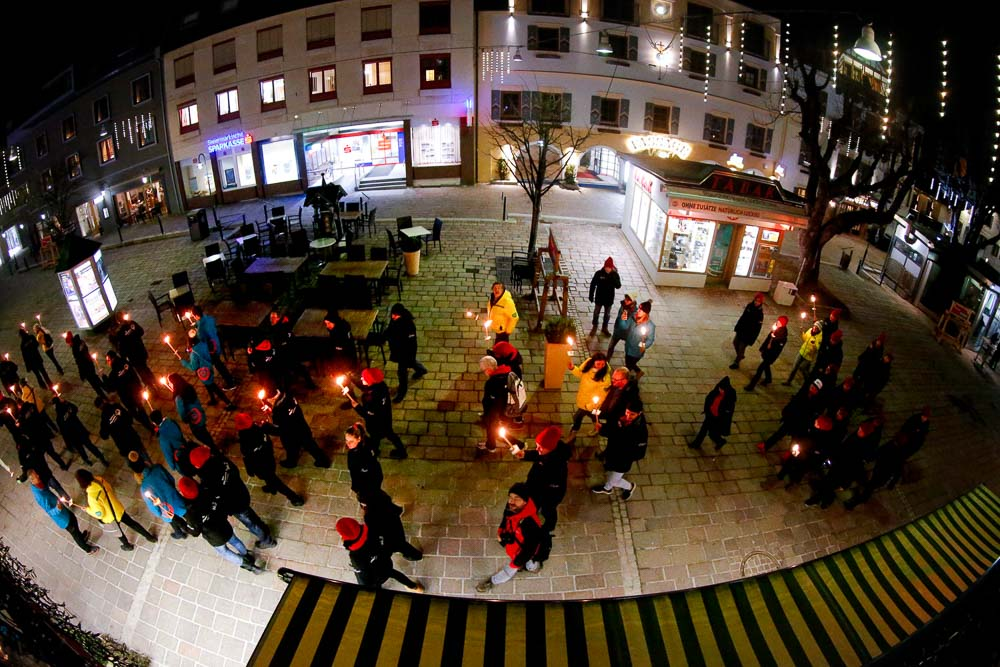 A fish-eye lens image of people walking with candles through a snowy street at night.