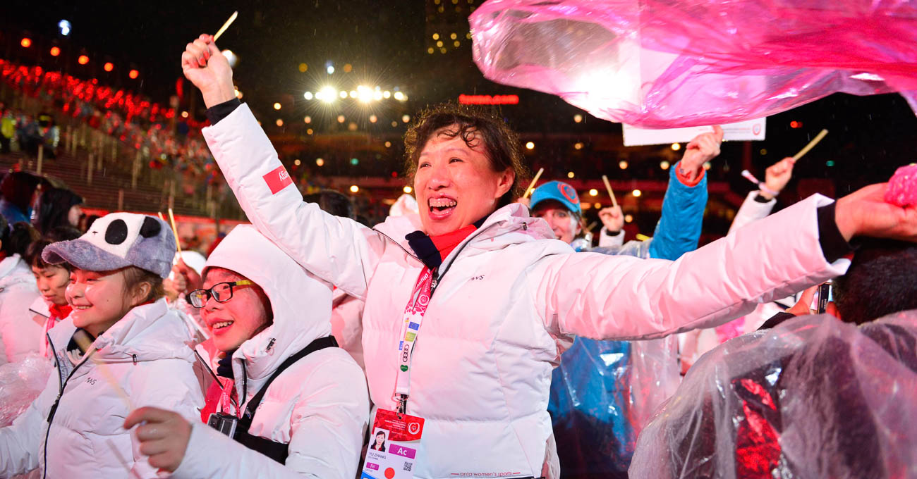 A woman with a joyful expression takes part in the parade of athletes