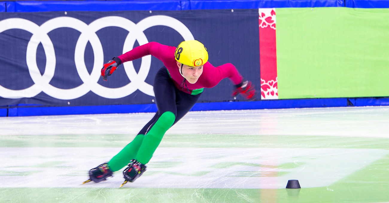 A speed skater quickly turns the corner on the ice during competition.