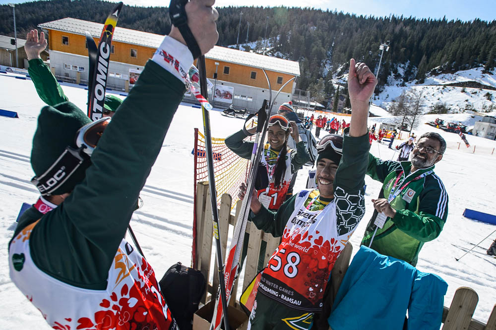 A skier holds his hands over his head, celebrating with his smiling teammates.