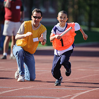 Volunteer cheers an athlete running with a baton