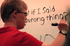 A man in red writing on the board