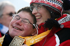 a man and a woman with hats and coats laughing and haveing a good time with a medal