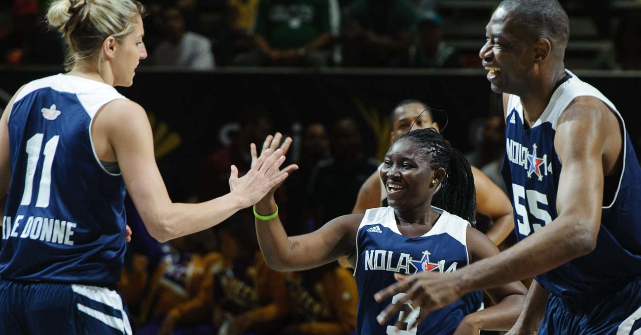 A smiling athlete high fives a much taller woman basketball player