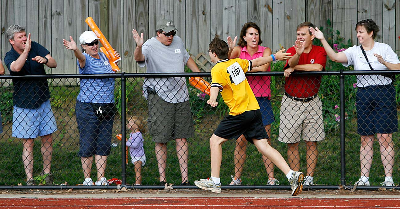 A runner passes a line of people who are giving high fives