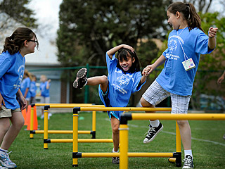 A youth helping a younger friend jump over a hurdle as they hold hands and laugh.