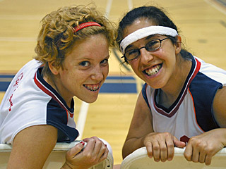 Two young female basketball players smiling for the camera during an exciting game.