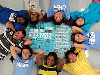 "A unified group of friends smiling and laying around a signed ""Spread the word to end the word"" poster."
