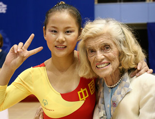 Eunice Kennedy Shriver poses with a smiling gymnast
