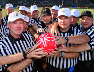 Referees in striped shirts join hands to hold a red football
