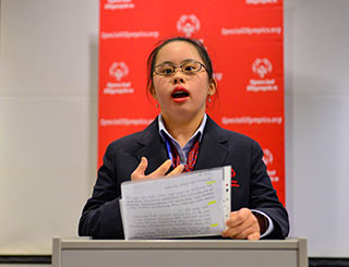 A young woman delivers a speech at a lectern.