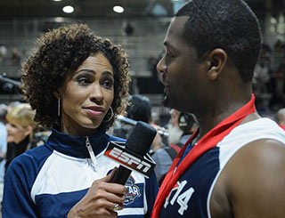 A woman with an ESPN microphone interviews a basketball player