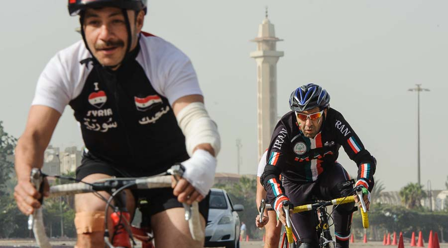 Cyclists race. A minaret is in the background