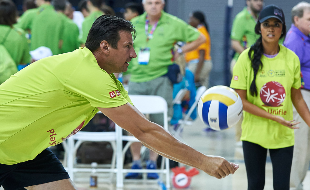 a man in green doing an action pose while the ball is coming to him