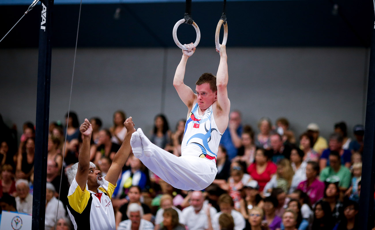 a man in white on the rings doing gymastics