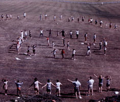 Distant photo of people lined up on an open field in concentric circles, doing exercises.