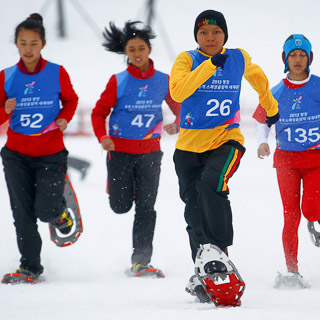 four woman running in snow shoes