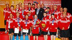 A team dressed in red wearing their medals