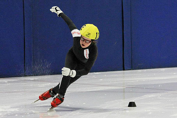A speedskater zooms over the ice in a tight turn
