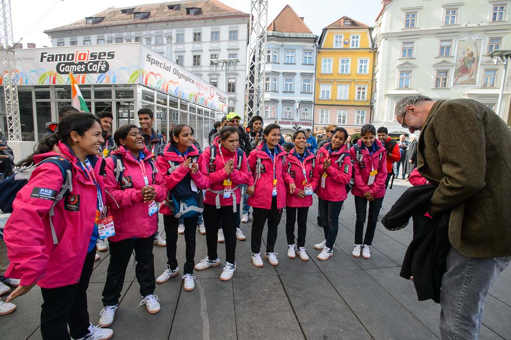 A group of eight young women in pink jackets clasp hands and bow as a man bows in return.