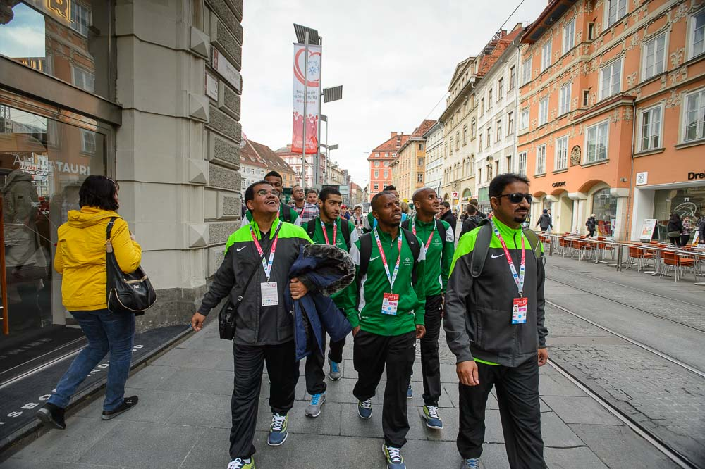 A group of young men in athletic gear walk on a sidewalk in the city of Graz.